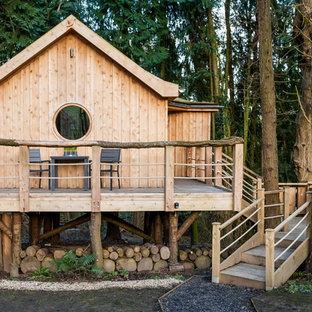 Esempio della facciata di una casa piccola marrone rustica a un piano con rivestimento in legno e tetto a capanna