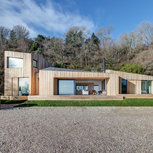 Brown contemporary two floor exterior in Hampshire with wood cladding and a lean-to roof.
