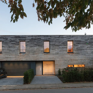 Medium sized and gey contemporary two floor detached house in London with wood cladding and a flat roof.