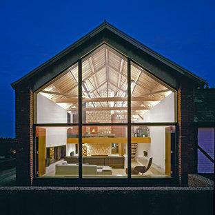 Ispirazione per la facciata di una casa contemporanea a un piano con rivestimento in vetro e tetto a capanna