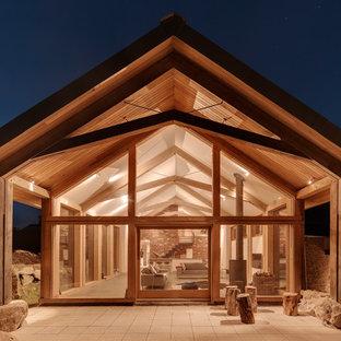 Foto della facciata di una casa contemporanea con rivestimenti misti e tetto a capanna