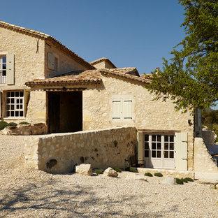 Cette photo montre une grande façade en pierre beige méditerranéenne à un étage avec un toit à deux pans.