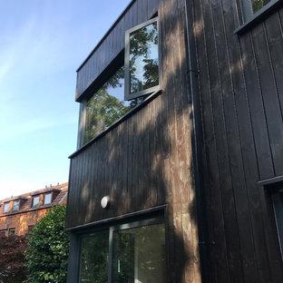 Imagen de fachada de casa negra, escandinava, de tamaño medio, de tres plantas, con revestimiento de madera, tejado a dos aguas y tejado de teja de barro