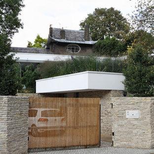 Foto della facciata di una casa bianca contemporanea a due piani di medie dimensioni con rivestimento in pietra