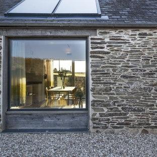 Diseño de fachada costera, de tamaño medio, a niveles, con revestimiento de piedra y tejado a dos aguas