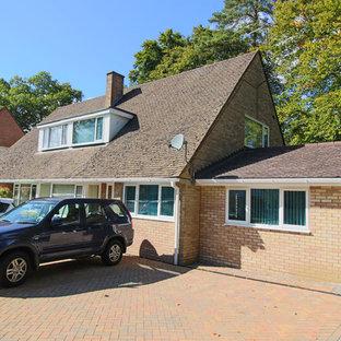 Imagen de fachada de casa bifamiliar beige, de estilo de casa de campo, extra grande, de una planta, con revestimiento de ladrillo, tejado a doble faldón y tejado de teja de barro