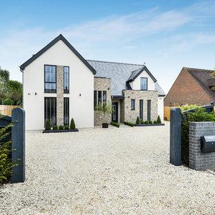 Imagen de fachada de casa blanca, actual, grande, de tres plantas, con revestimiento de piedra y tejado a cuatro aguas