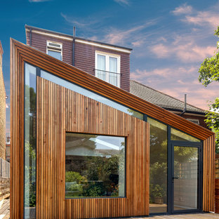 Large and brown contemporary one floor detached house in London with wood cladding and a lean-to roof.