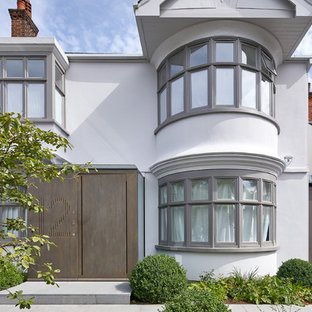 Photo of a white classic two floor render detached house in London.