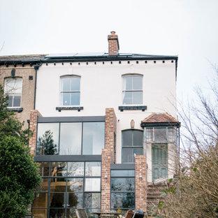 他の地域のインダストリアルスタイルのおしゃれな家の外観 (レンガサイディング、マルチカラーの外壁、デュープレックス、混合材屋根) の写真
