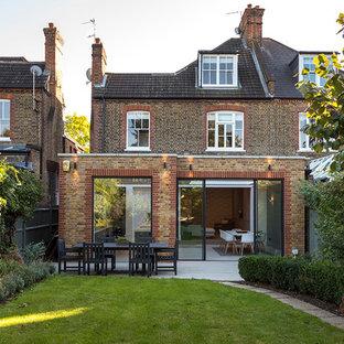 他の地域のトラディショナルスタイルのおしゃれな家の外観 (レンガサイディング、茶色い外壁、タウンハウス) の写真