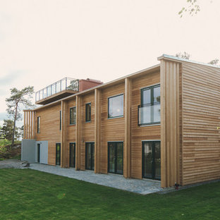 Huge scandinavian beige two-story wood exterior home idea in Stockholm with a shed roof