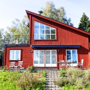 Foto de fachada roja, escandinava, de tamaño medio, de dos plantas, con revestimiento de madera y tejado de un solo tendido