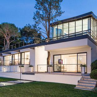 Exemple d'une grande façade de maison blanche tendance à un étage avec un toit plat.