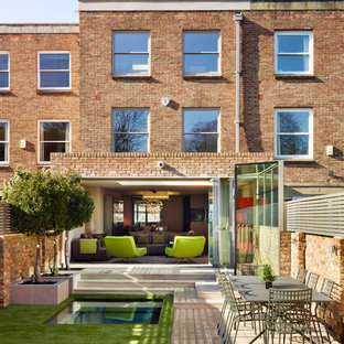Inspiration for a contemporary brick exterior in London with three or more floors and a flat roof.