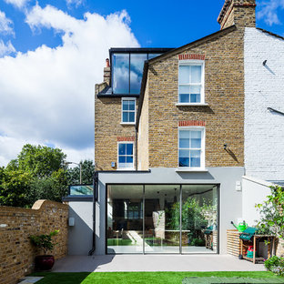 This is an example of a brown traditional brick exterior in London with three floors and a pitched roof.
