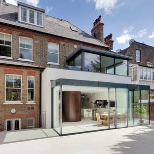 Large contemporary multicolored three-story brick exterior home idea in London with a tile roof