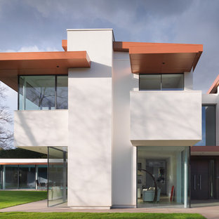 This is an example of a large and white contemporary two floor render detached house in London with a flat roof.