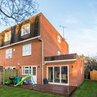 Foto de fachada de casa bifamiliar marrón, actual, de tamaño medio, de tres plantas, con tejado a doble faldón y tejado de varios materiales