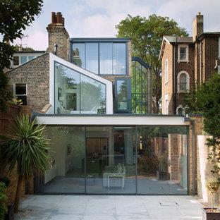 Idéer för stora funkis flerfamiljshus i flera nivåer, med glasfasad och platt tak