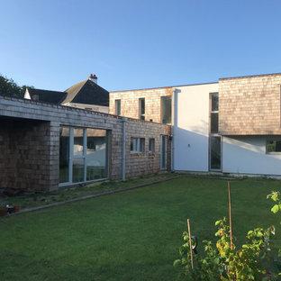 デヴォンの中くらいのミッドセンチュリースタイルのおしゃれな家の外観 (木材サイディング、オレンジの外壁、緑化屋根) の写真