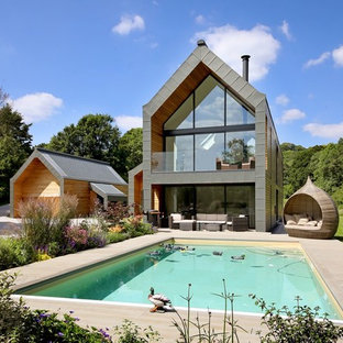 This is an example of a gey rural two floor glass detached house in Surrey with a pitched roof.
