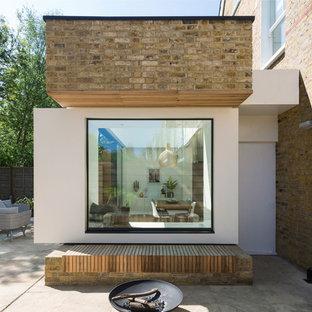 На фото: трехэтажный, кирпичный, желтый частный загородный дом в современном стиле с крышей из смешанных материалов с