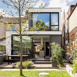 Inspiration for a white contemporary two floor render exterior in London with a flat roof.