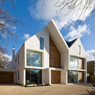 Large trendy white three-story mixed siding house exterior photo in London