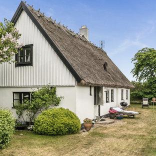 Lantlig inredning av ett mellanstort vitt hus, med två våningar och sadeltak