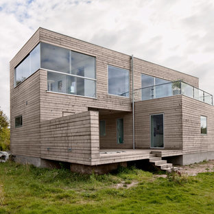 Large urban beige two-story wood flat roof photo in Gothenburg