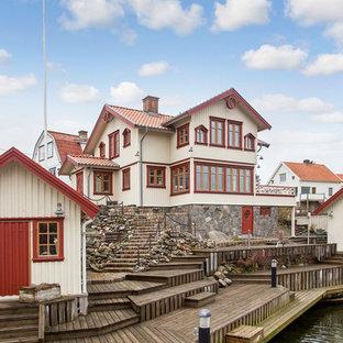 Foto på ett stort skandinaviskt beige trähus, med två våningar och sadeltak