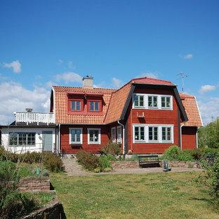 Foto på ett lantligt rött hus, med två våningar, mansardtak och tak i mixade material