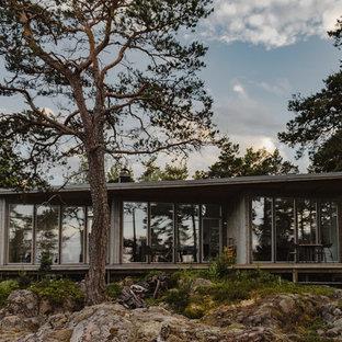 Minimalistisk inredning av ett mellanstort hus, med allt i ett plan, glasfasad och platt tak