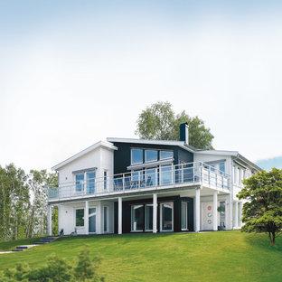 Diseño de fachada blanca, escandinava, extra grande, de dos plantas, con revestimiento de madera y tejado de un solo tendido