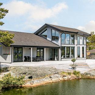 Bild på ett stort skandinaviskt beige trähus, med två våningar och sadeltak