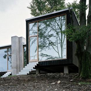 Kleines, Zweistöckiges, Schwarzes Modernes Haus mit Holzfassade und Flachdach in Stockholm