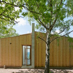 Bild på ett mycket stort funkis beige trähus, med allt i ett plan och sadeltak