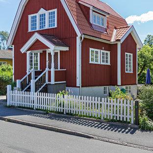 Lantlig inredning av ett stort rött hus, med tre eller fler plan, mansardtak och tak med takplattor