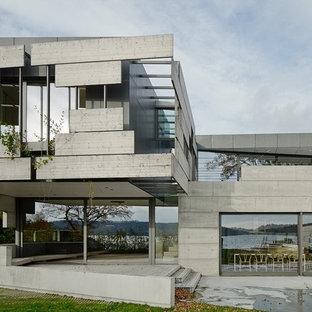 Idéer för ett stort modernt grått betonghus, med två våningar och platt tak