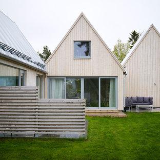 ストックホルムの中くらいの北欧スタイルのおしゃれな家の外観 (木材サイディング、ベージュの外壁、タウンハウス) の写真