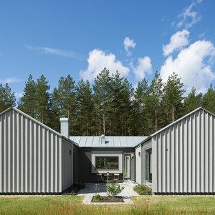 Inspiration för ett mycket stort industriellt grått hus, med två våningar, metallfasad och sadeltak