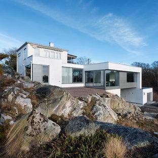 Foto de fachada blanca, nórdica, extra grande, de tres plantas, con revestimiento de piedra y tejado plano