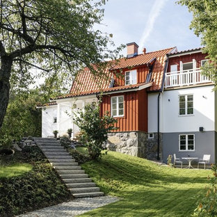 Mid-sized danish white three-story stone exterior home photo in Stockholm with a clipped gable roof