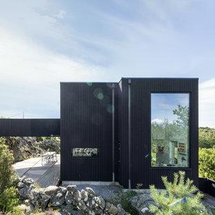 Imagen de fachada negra, moderna, de tamaño medio, con revestimiento de madera