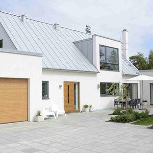 Modelo de fachada blanca, nórdica, grande, de dos plantas, con tejado a dos aguas y revestimiento de hormigón