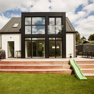 Foto de fachada blanca, nórdica, de dos plantas, con revestimientos combinados y tejado a dos aguas