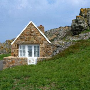 Imagen de fachada multicolor, escandinava, pequeña, de una planta, con revestimiento de piedra y tejado a la holandesa