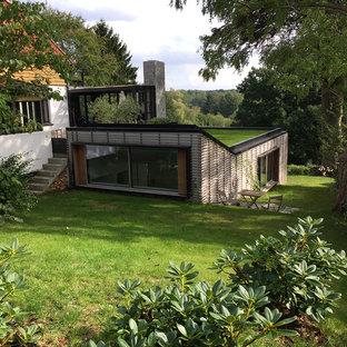 Inspiration for a large scandinavian brown split-level mixed siding flat roof remodel in Copenhagen