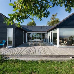 Cette image montre une grand façade en bois noire nordique de plain-pied avec un toit à deux pans.